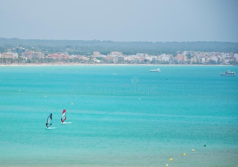 Turquoise bay with windsurfers. PALMA DE MALLORCA, SPAIN - JULY 14, 2012: Turquoise bay with windsurfers on a sunny summer day on July 14, 2012 in Mallorca stock images