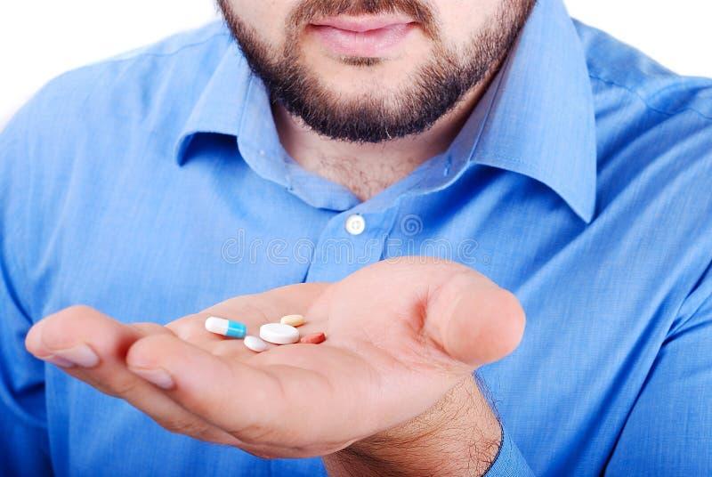 Palma del hombre con las píldoras de la medicina encendido imagenes de archivo