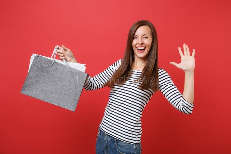 Palma engraçada da exibição da jovem mulher, mão de ondulação, guardando sacos dos pacotes com compras após a compra isolada no v fotografia de stock royalty free