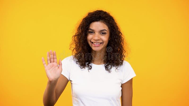 Palma fêmea afro-americana amigável da exibição, mão de ondulação na câmera, dando boas-vindas imagem de stock royalty free