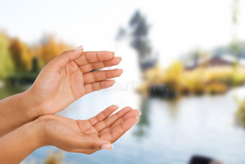 Palma fêmea preta da mão dois acima, handbreadth no fundo borrado do rio Front View Zombaria acima Copie o espaço imagens de stock royalty free