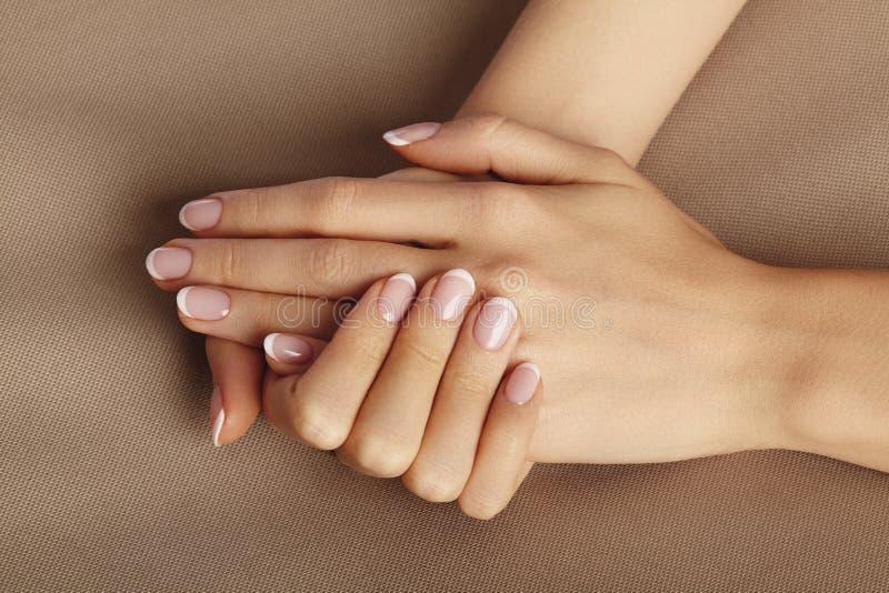 Palma femenina joven Manicura hermosa del encanto Estilo francés Pulimento de clavo Cuide sobre las manos y los clavos, piel limp imagen de archivo libre de regalías