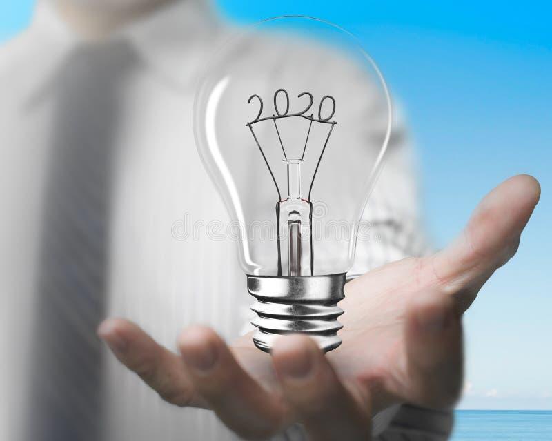 Palma maschile con lampadina con 2020 forme metalliche fotografia stock