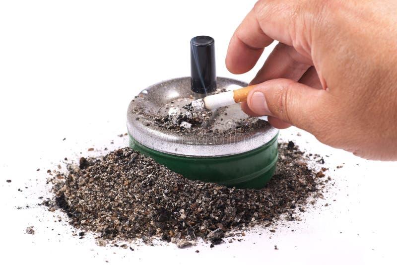 Palma que chasquea la ceniza de cigarrillo en el cenicero fotografía de archivo