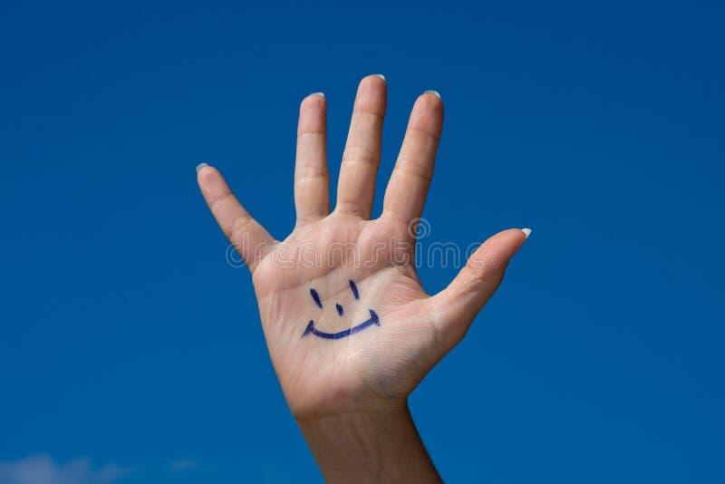 Palma umana con il sorriso fotografie stock