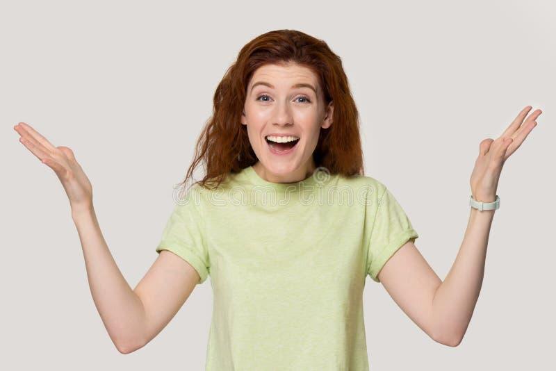 Palmas felices emocionadas del aumento de la mujer del pelirrojo que presentan en fondo gris fotos de archivo