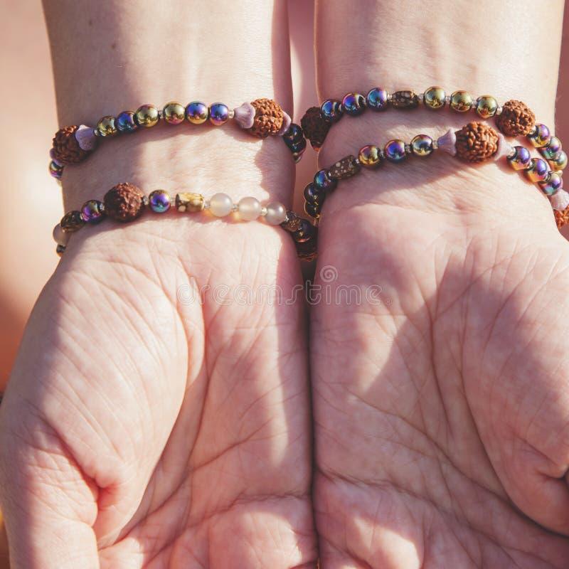 Palmas femeninas con las pulseras naturales imágenes de archivo libres de regalías