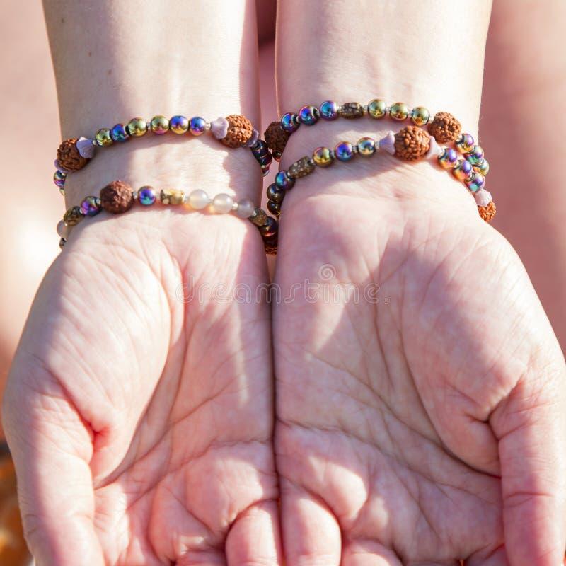 Palmas femeninas con las pulseras naturales fotografía de archivo libre de regalías