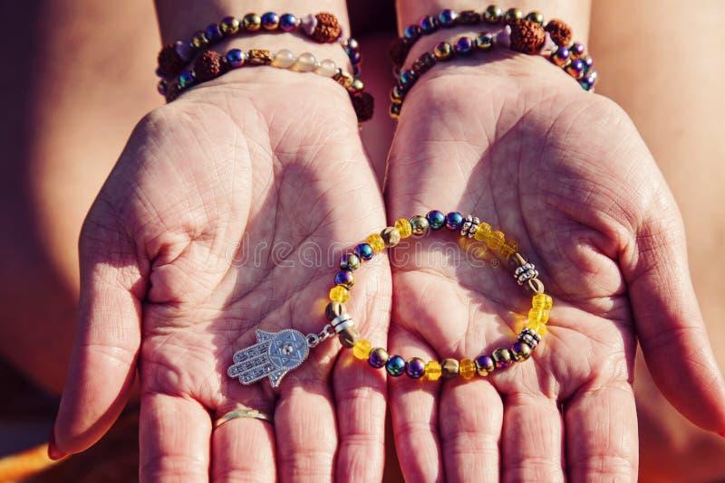 Palmas femeninas con las pulseras naturales de la gota que sostienen la pulsera con el colgante del hamsa fotografía de archivo