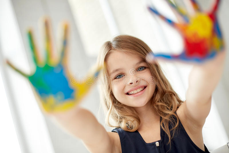Palmas pintadas demostración feliz de la mano de la muchacha en casa foto de archivo libre de regalías