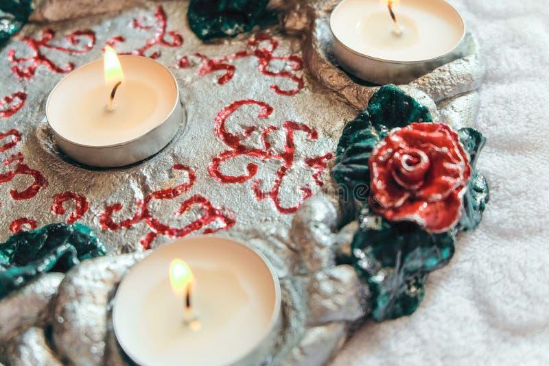 Palmatoria hecha a mano del soporte decorativo con las velas ardientes foto de archivo