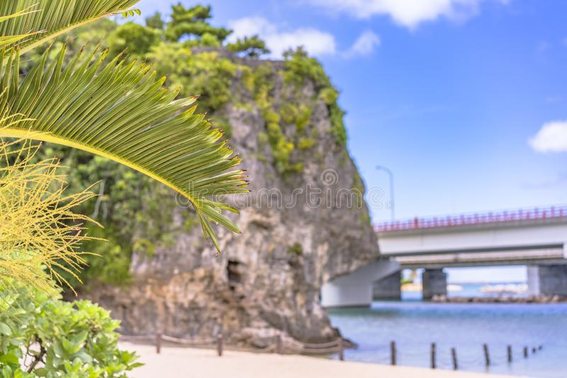 A palmeira no Sandy Beach Naminoue cobriu por uma rocha enorme com um santu?rio xinto?smo na parte superior de um penhasco e de u foto de stock