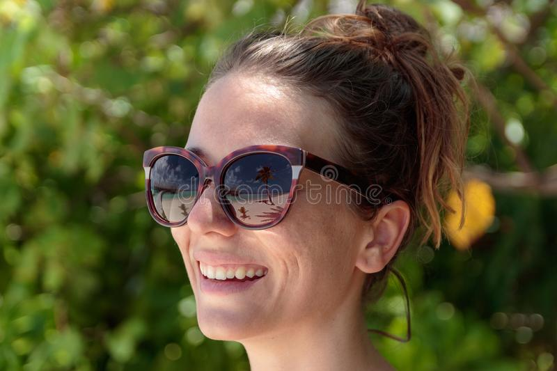 Palmeira, praia branca e água azul claro refletidas nos óculos de sol de uma mulher feliz maldives imagem de stock