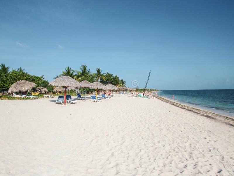 Palmen en wit zandig strand bij de zonsondergang in Caribbeans stock fotografie