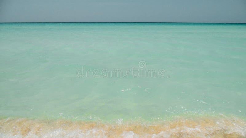 Palmen en wit zandig strand bij de zonsondergang in Caribbeans stock afbeelding