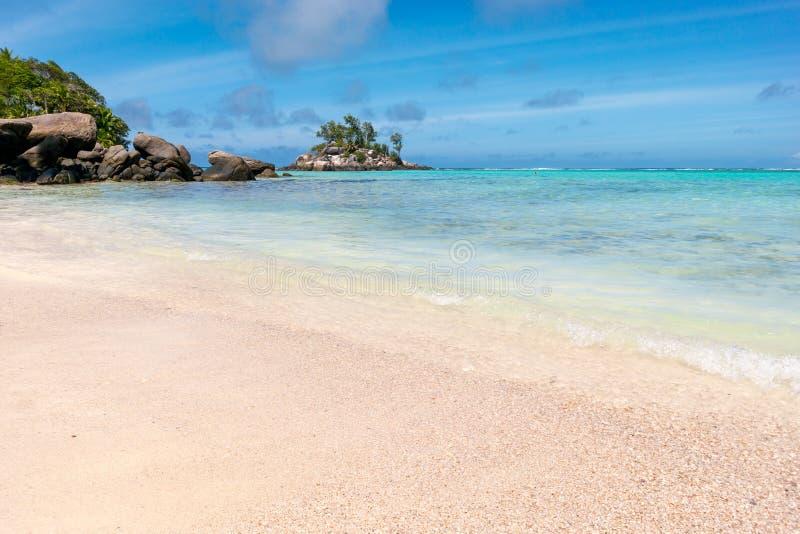 Palmen, wit zand en turkooise overzees bij Sprookjeslandstrand, Seychellen Afrika stock afbeeldingen