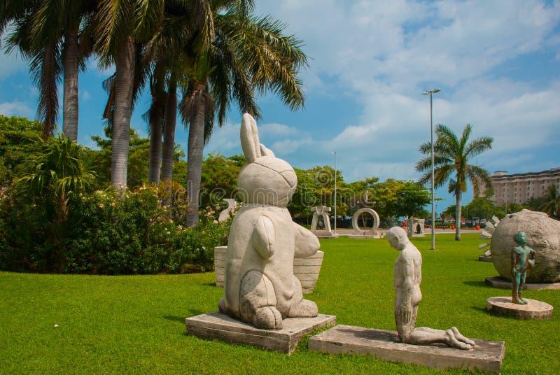 Palmenpark Ongebruikelijke monumenten dichtbij Cancun Mexico de hazen en de man op zijn knieën stock foto