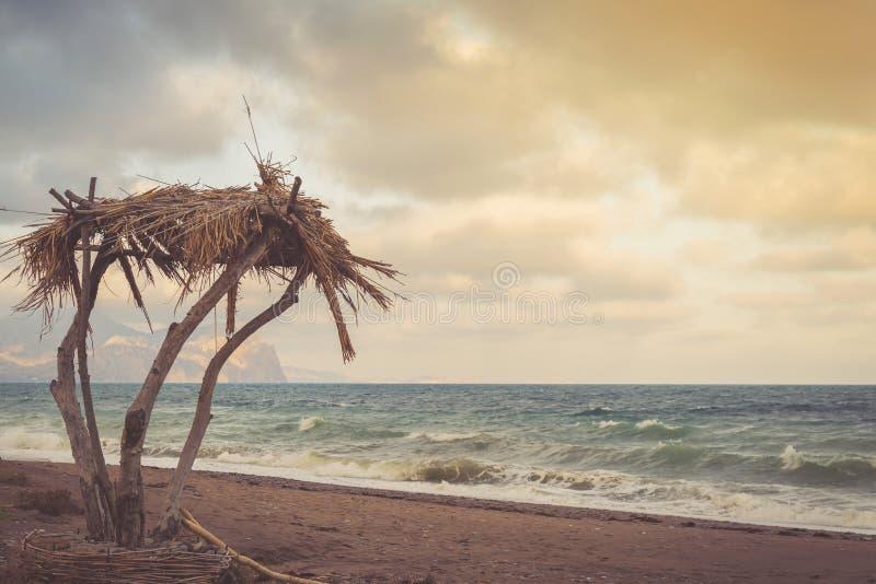 Palmera, casa de planta baja contra el mar tempestuoso azul en la puesta del sol foto de archivo