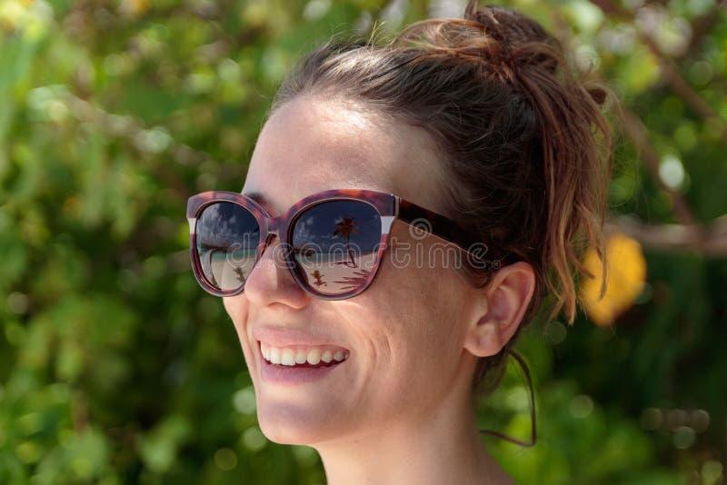 Palmera, playa blanca y agua azul cristalina reflejadas en las gafas de sol de una mujer feliz maldives imagen de archivo