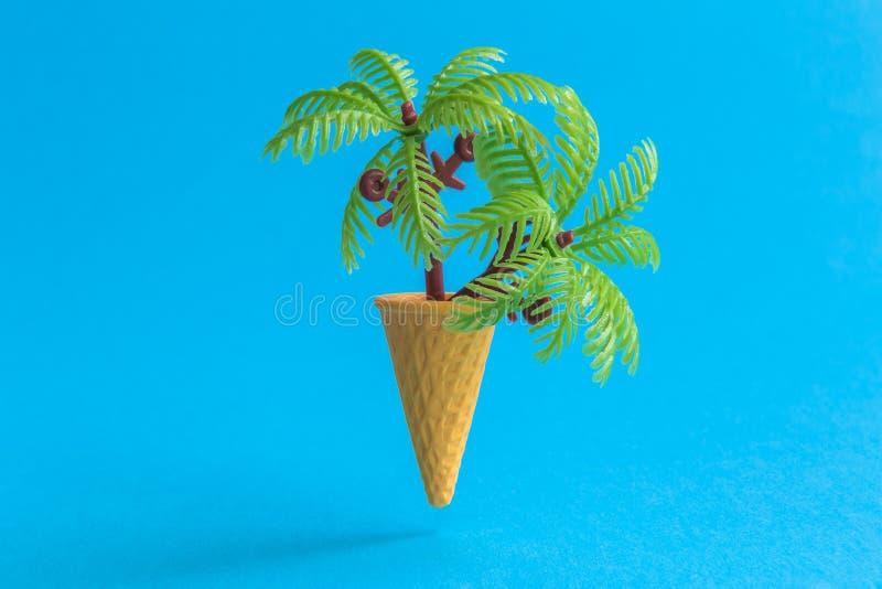 Palmeras en el extracto del cono de helado aislado en azul fotografía de archivo