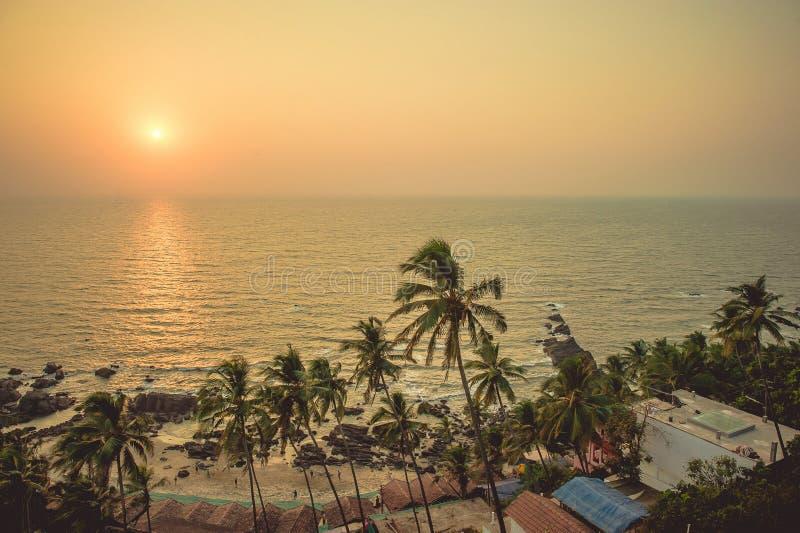 Palmeras en los rayos de la puesta del sol en la playa del fondo y fotografía de archivo