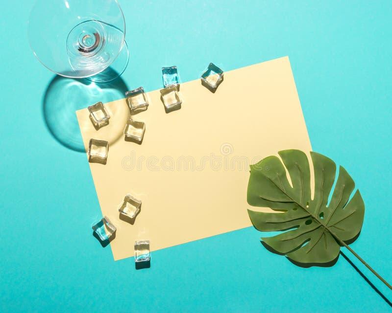 Palmette tropicale avec le verre de martini et les gla?ons sur le fond bleu lumineux Composition minimale en ?t? Configuration pl photos libres de droits