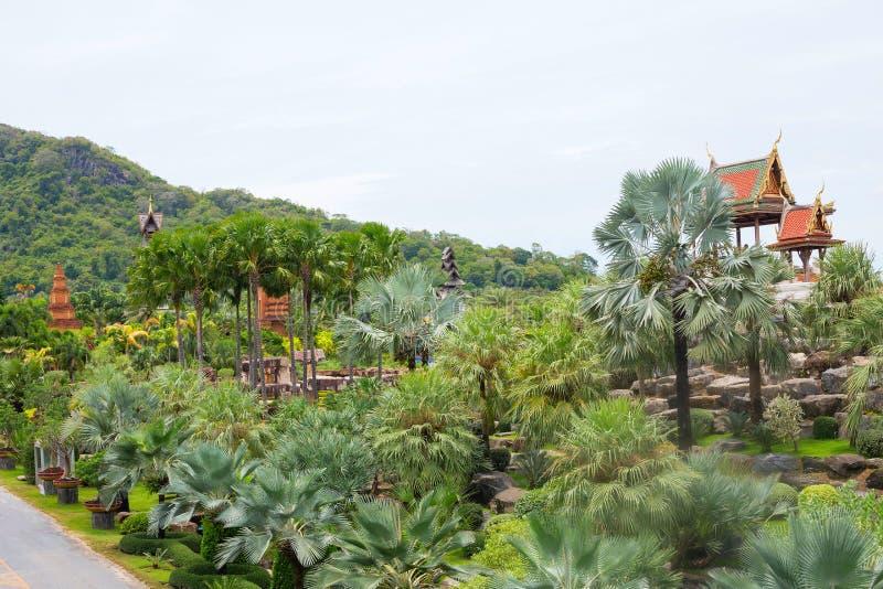 Palmiers énormes, montagnes, bâtiments bouddhistes photos stock