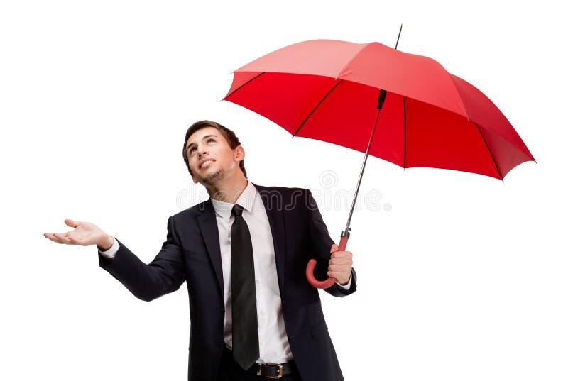 Palming herauf Geschäftsmann mit rotem Regenschirm überprüft den Regen stockbild