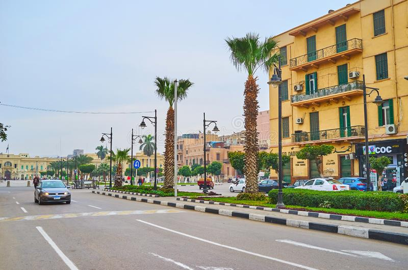 The palms in El Tahrir avenue, Cairo, Egypt. CAIRO, EGYPT - DECEMBER 22, 2017: Walk El Tahrir avenue with a view on slender palm trees, stores, residential stock photo