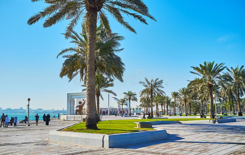 Palms on seaside promenade of Doha, Qatar. DOHA, QATAR - FEBRUARY 13, 2018: The rows of lush palm trees in park, located in Corniche promenade, stretching along stock photography