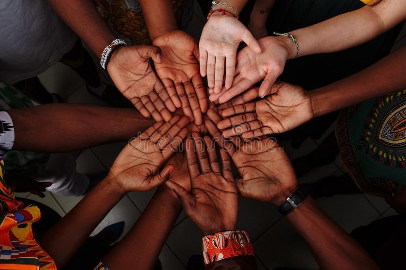 Palms up hands of happy group of multinational African, latin american and european people which stay together in circle.  stock photography