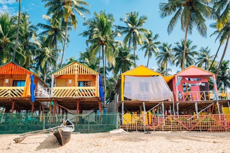 Palmträd och bungalowen i Palolem sätter på land, Goa, Indien arkivfoto
