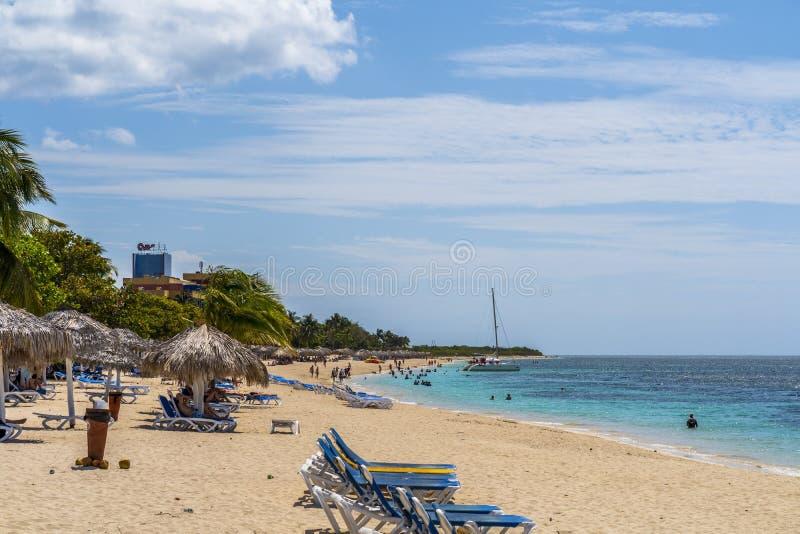 Palmträd och paraplyer på den strandPlaya anconen nära Trinidad arkivbild