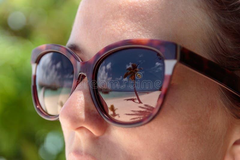 Palmträd, vit strand och kristallklart blått vatten reflekterade i solglasögon av en kvinna Maldiverna royaltyfri bild