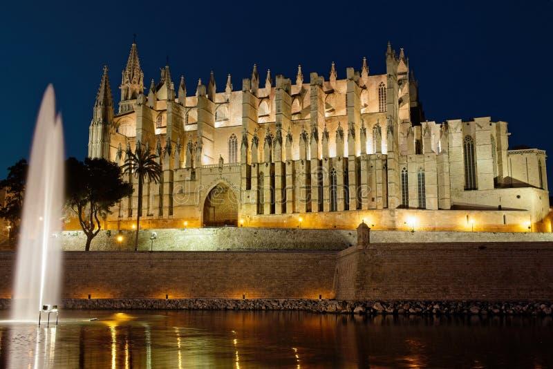 Palmy katedra iluminująca przy półmrokiem z jeziorem, fontanną i odbiciami na wodzie, Mallorca, Spain zdjęcia royalty free