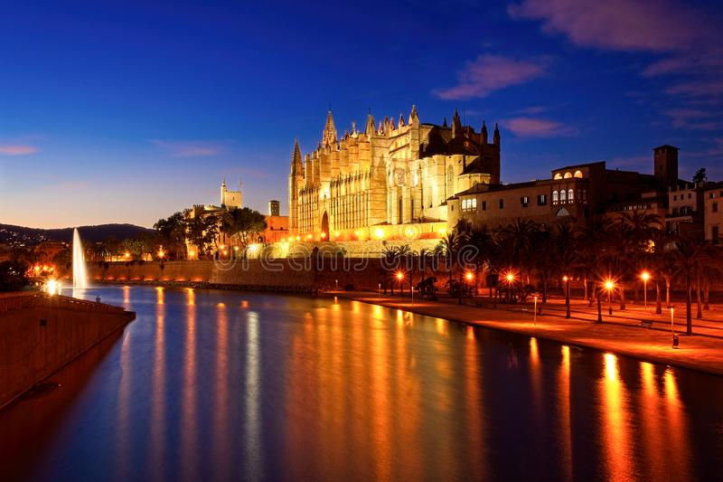 Palmy katedra iluminuj?ca przy p??mrokiem z jeziorem, fontann? i odbiciami na wodzie, Mallorca, Spain obrazy royalty free