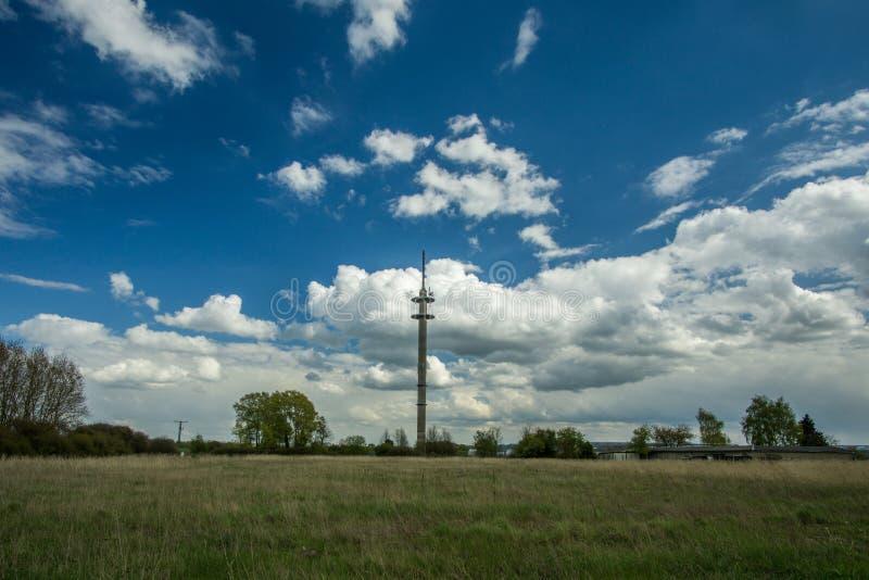 Palo del transmisor con el prado verde imagenes de archivo