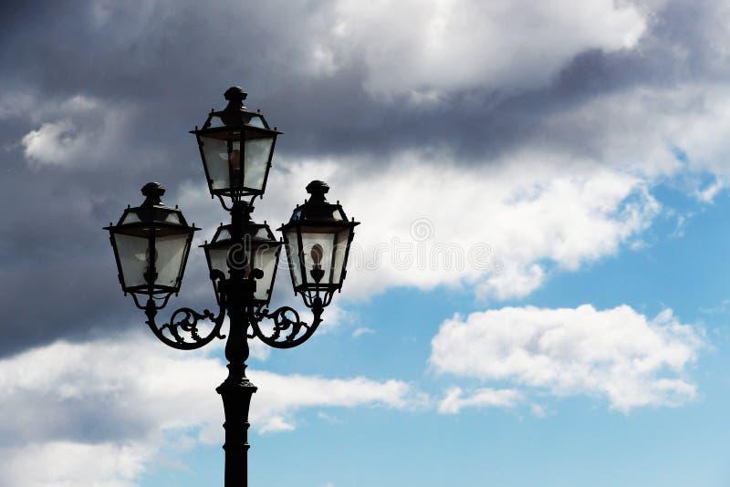 Palo della luce antico contro un cielo nuvoloso immagini stock libere da diritti