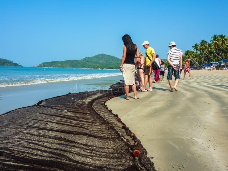 """PALOLEM, GOA, †de la INDIA """"22 de febrero de 2011: Turistas que miran una red de pesca que miente en la arena cerca del agua imagenes de archivo"""
