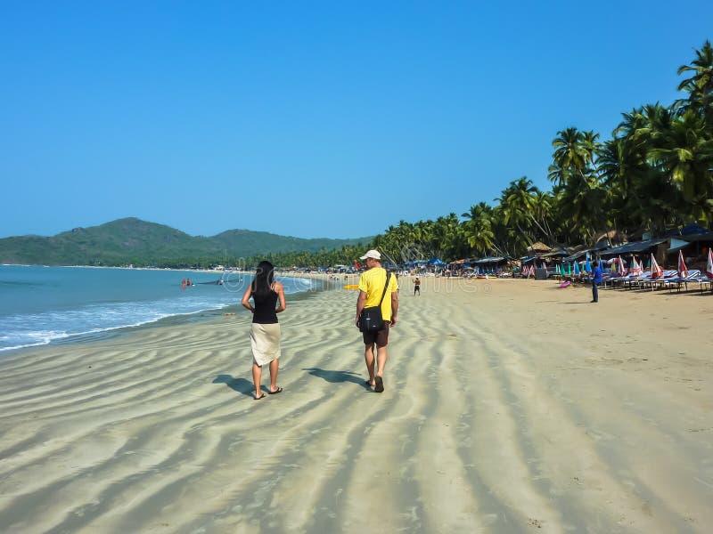 PALOLEM, GOA, ΙΝΔΊΑ †«στις 22 Φεβρουαρίου 2011: Ένα ζεύγος τουριστών που περπατά κατά μήκος της παραλίας στοκ φωτογραφίες