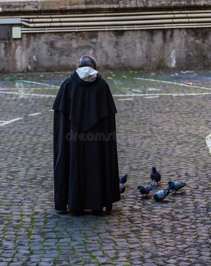 Palomas de alimentación del monje benedictino en la calle, Roma, Italia imagen de archivo