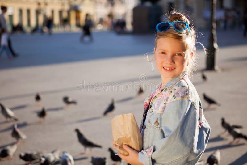 Palomas de alimentación de la niña adorable al aire libre fotografía de archivo libre de regalías