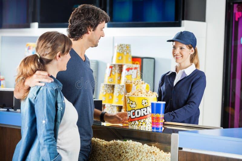 Palomitas de compra de los pares expectantes en el cine foto de archivo libre de regalías