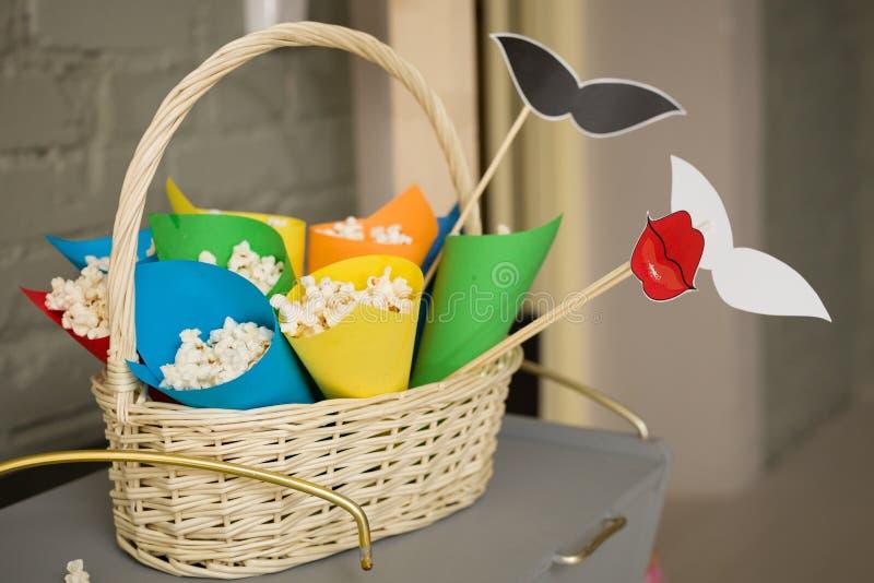 Palomitas de maíz en conos de papel coloridos en una cesta blanca Preparaciones para un partido accesorios por un día de fiesta d fotos de archivo