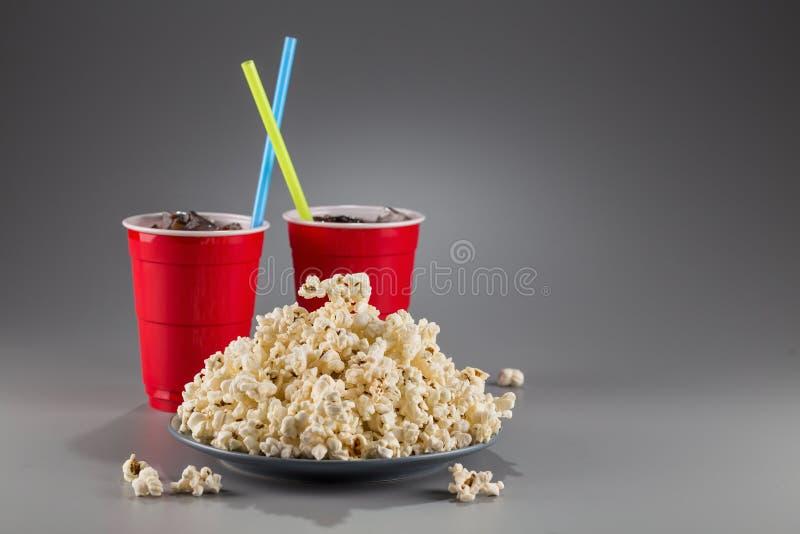 Palomitas del primer en el fondo de tazas plásticas rojas con la bebida efervescente con la paja coloreada fotografía de archivo libre de regalías