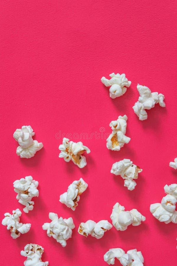 Palomitas saladas sabrosas en fondo rosado Endecha plana de la palomitas de maíz Visión superior Comida, concepto del bocado Boca foto de archivo libre de regalías