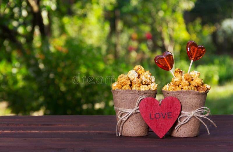 Palomitas y piruletas de oro dulces Fije para los amantes Popokorn en corazones de un cubo de papel y del caramelo Concepto román imágenes de archivo libres de regalías