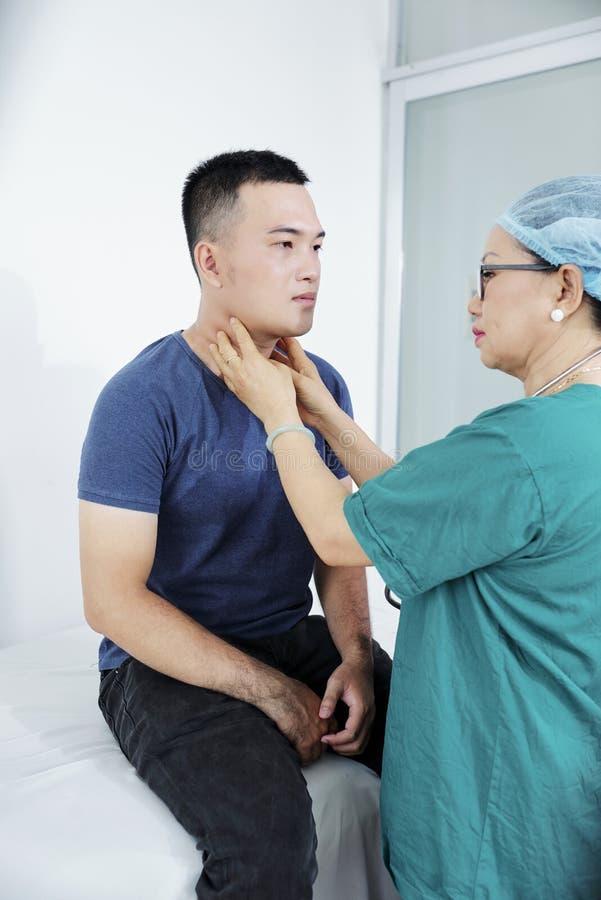 Palpating λαιμός γιατρών του ατόμου στοκ φωτογραφίες