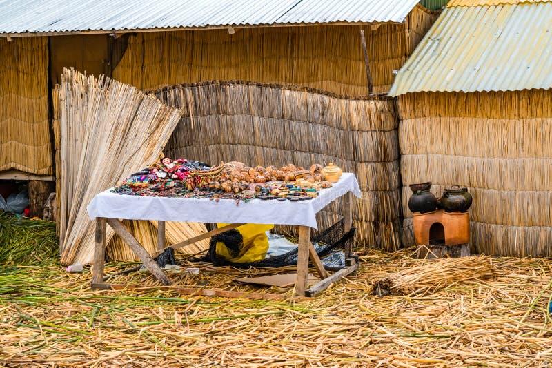 Pamiątka dla sprzedaży na drewnianym stole i część robić Totora płochy na Spławowej Uros wyspie na Jeziornym Titicaca dom zdjęcia stock