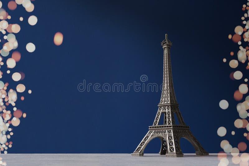 Pamiątkarska wieża eifla na błękitnym tle z kolorowym bokeh zaświeca jako rama zdjęcia stock